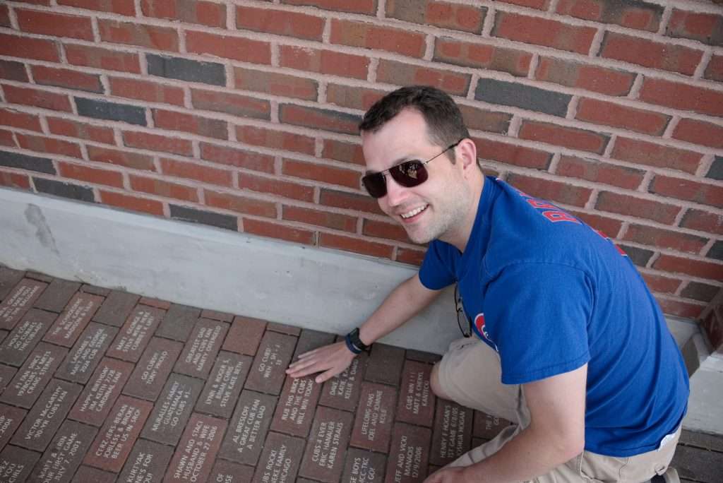 "My brother by our Wrigley Field brick in 2016. ""Rub this brick and the Cubs will win today"""