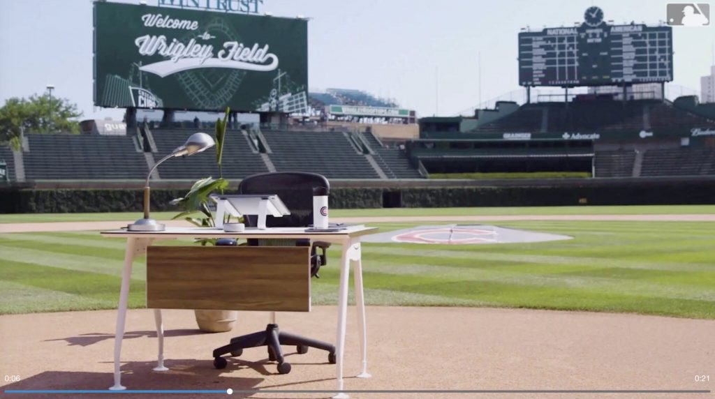 A work desk and work chair positioned over home plate at Wrigley Field. Desk holds a silver lamp, Cubs mug, laptop holder. No extension cord seen.